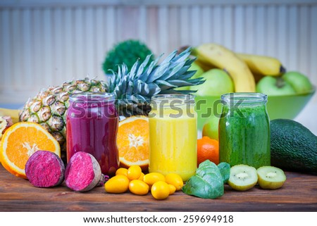 Blended green,yellow and purple smoothie with ingredients selective focus #259694918