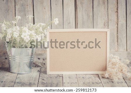 Blank corkboard and potted flowers by wooden background. #259812173