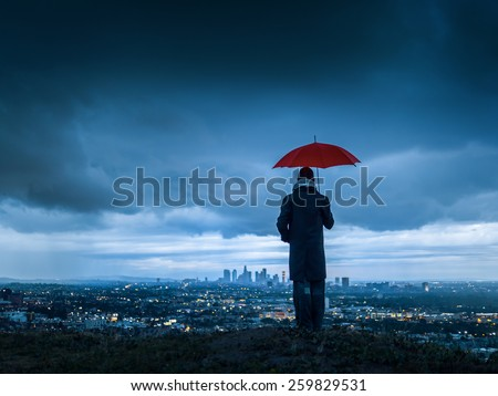 Man under red umbrella overlooking stormy Los Angeles cityscape from Hollywood Hills at twilight.  #259829531