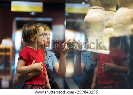Woman and child looking old ancient amphora in historical museum Royalty-Free Stock Photo #259843295