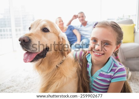 Portrait of happy girl with dog while parents relaxing in background at home #259902677