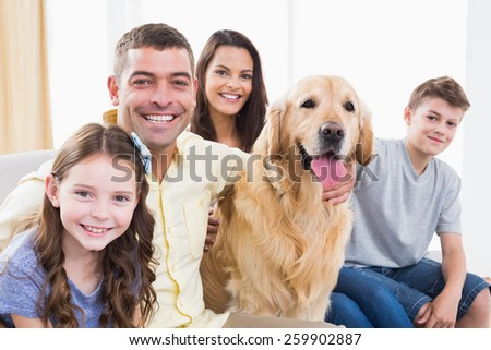 Portrait of smiling family sitting with Golden Retriever on sofa at home #259902887