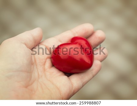 Young woman holds out a red heart in her hand, concept of love, kindness and empathy #259988807