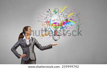 Young businesswoman holding light bulb in palm #259999742