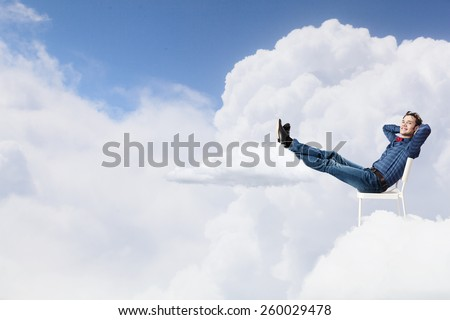 Young man sitting in chair with legs up and relaxing #260029478