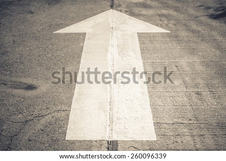 Arrow straight traffic sign on concrete road