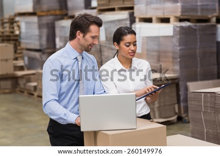 Warehouse managers working on laptop in a large warehouse #260149976