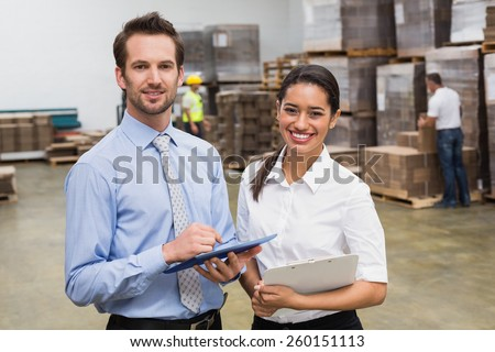 Smiling warehouse managers working together in a large warehouse #260151113