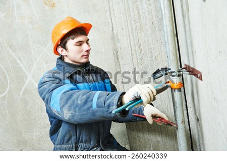 industrial plumber fixing pipe in water heating engineering system of building  #260240339