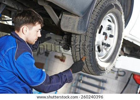auto service man worker measuring rubber car wheel tyre protector #260240396