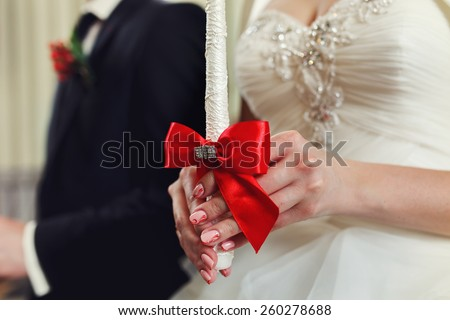 The groom and the bride with candles. Wedding ceremony in church #260278688