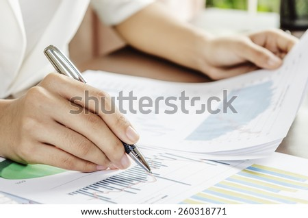 Woman evaluating charts and documents on paper #260318771