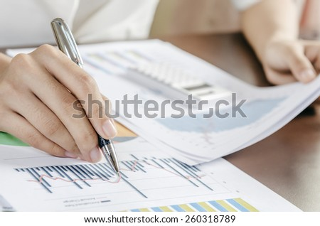 Woman evaluating charts and documents on paper #260318789