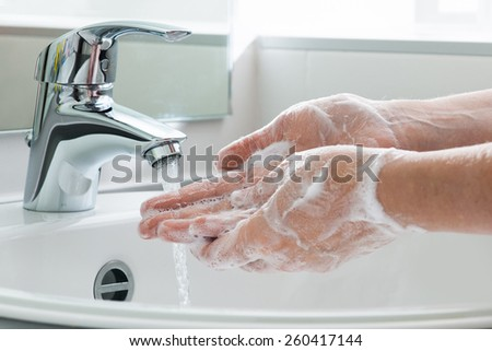 Hygiene concept. Washing hands with soap under the faucet with water Royalty-Free Stock Photo #260417144