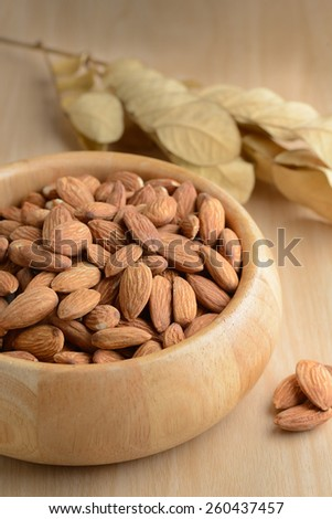 Almonds in wooden bowl on table. #260437457