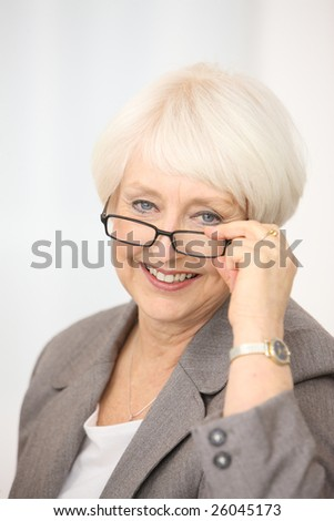 Professional senior businesswoman looking over glasses #26045173