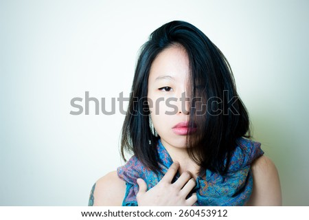 Young asian woman close up posing with blue foulard around neck, looking at camera color effect background #260453912