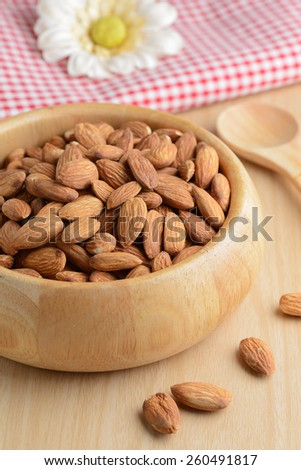 Almonds in wooden bowl on table. #260491817