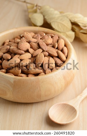 Almonds in wooden bowl on table. #260491820