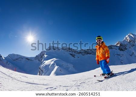 Fisheye view of boy skiing on mountain slope #260514251