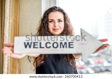 Young woman holding arrow sign with word. #260700413