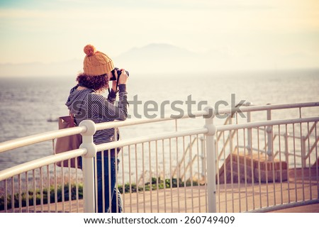 A vintage photo of a girl taking photo near the seaside #260749409