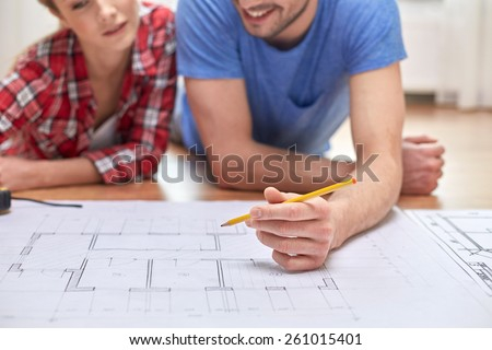repair, building, renovation and people concept - close up of happy couple looking at blueprint at home #261015401