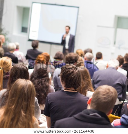 Speaker at Business Conference and Presentation. Audience in the conference hall. Business and Entrepreneurship. Copy space on white screen. #261164438