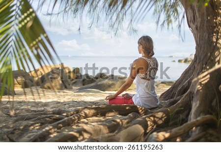 Meditation. photo of a woman who is sitting in the lotus position #261195263