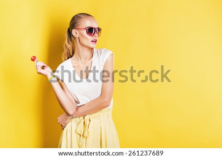 attractive woman in white top with lollipop in hand on yellow background #261237689