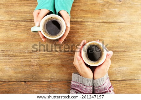 Female hands holding cups of coffee on rustic wooden table background #261247157