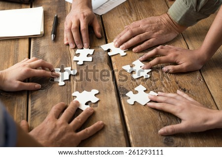 Closeup of businessman and woman with jigsaw puzzle pieces in office  Royalty-Free Stock Photo #261293111