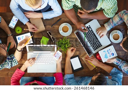 High angle view of people communicating at table with their devices Royalty-Free Stock Photo #261468146