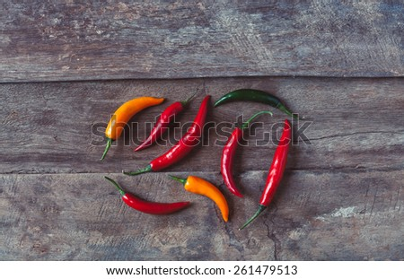 Hor chili peppers on a wooden background. Asian and mexican spice photo taken from the top.  #261479513