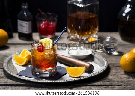 Old Fashioned Cocktail in Vintage Inspired Bar with Liquor Bottles and Ingredients Royalty-Free Stock Photo #261586196