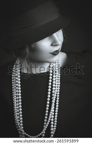 Black-white portrait of young beauty dark hair girl in vintage chanel 1920 style in red hat