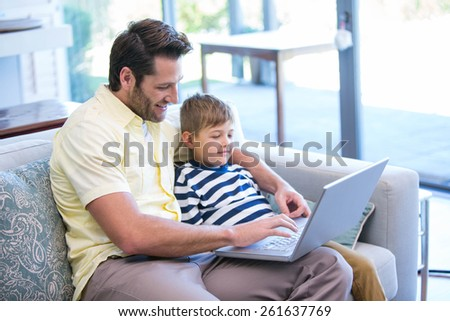 Father and son using laptop on the couch at home in the living room #261637769
