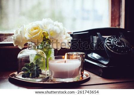 Bouquet of white flowers in a vase, candles on a copper vintage tray, old rotary phone, retro home decor #261743654