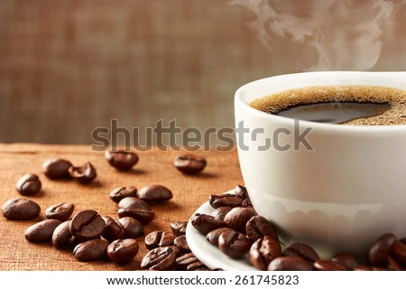 Coffee cup and coffee beans on table #261745823