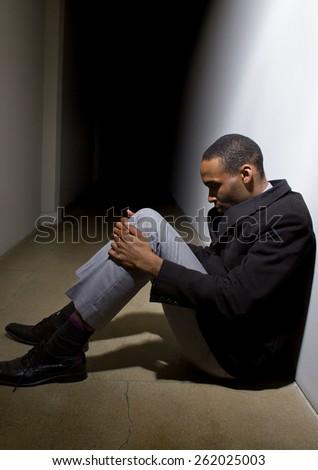 depressed man who lost faith sitting alone in a dark hallway #262025003