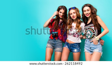 Three best friends posing in studio, wearing summer style outfit and jeans shorts  against blue background. Girls smiling and having fun. #262118492