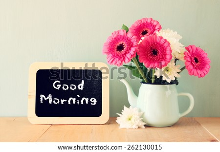 blackboard with the phrase good morning written on it next to fresh flowers