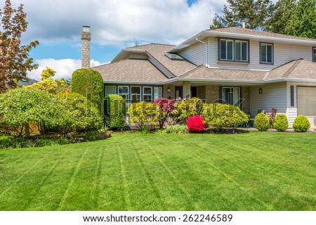 Luxury house with freshly mown grass lawn. Home exterior. #262246589