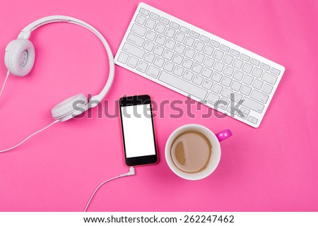 High angle view of white wireless keyboard, smart phone with isolated white screen, coffee in pink cup and white headphones on pink background. Horizontal, no retouch, copy space.