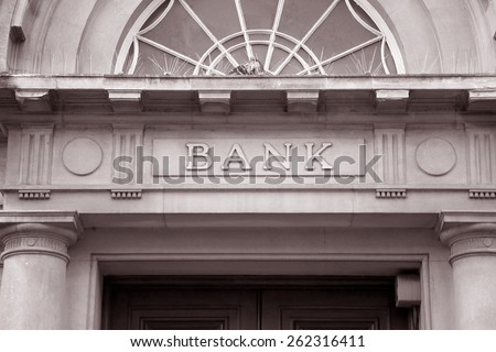 Bank Sign over Entrance Door in Black and White Sepia Tone Royalty-Free Stock Photo #262316411