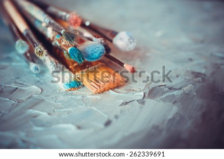 Paintbrushes on artist canvas covered  with oil paints Royalty-Free Stock Photo #262339691