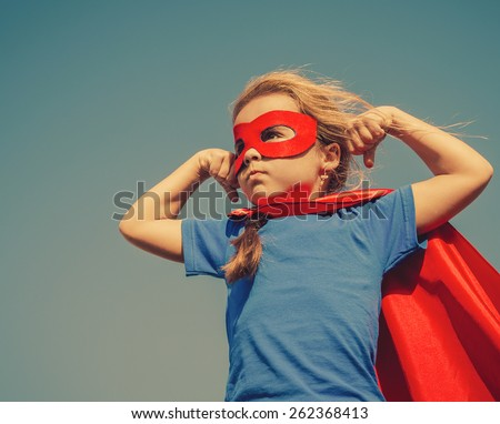 Funny little power super hero child (girl) in a red raincoat. Superhero concept. Instagram colors toning Royalty-Free Stock Photo #262368413