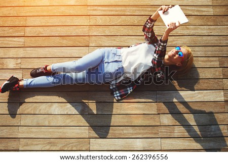 High angle shot of a pretty young woman pouting for a self-portrait while lying on wooden jetty enjoying the sun, cute tourist girl taking self-ie with digital tablet camera outdoors, flare sun light