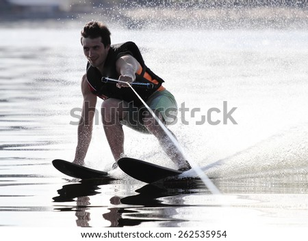 Athlete water skiing and have fun. Summer by the sea.A water skier in his 60's preforming water skiing sport on a lake. #262535954