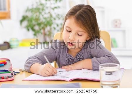 Little kid at home doing homework #262543760